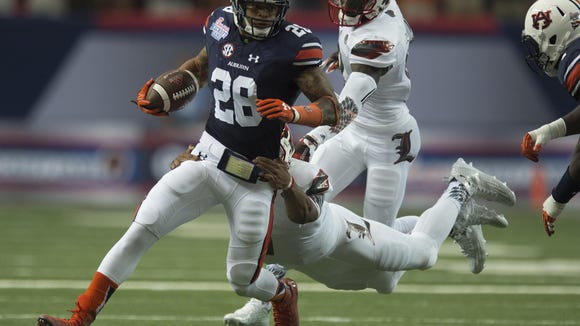 Auburn defensive back Tray Matthews runs downfield as Louisville quarterback Reggie Bonnafon attempts to tackle him after he intercepted a pass on the first play from scrimmage on Saturday at the Georgia Dome in Atlanta.
