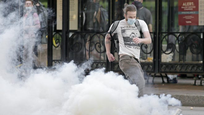 A protester kicks a canister of tear gas back toward police on May 28, the third day of protests Downtown. Mayor Andrew J. Ginther issued a directive Tuesday barring police from using tear gas and other chemical agents against peaceful protesters.