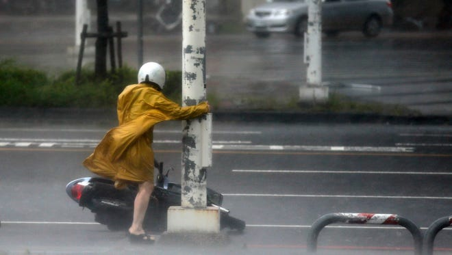 A motorist holds on to a post as she braves high winds and rain of Super Typhoon Meranti in Kaohsiung, southern Taiwan, 14 Sept. 2016.