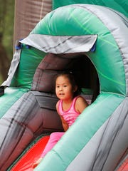 A young Riverfest visitor prepares to head down the slide of a bounce house during Saturday's festival.