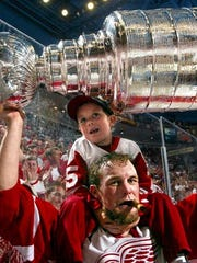 Darren McCarty with his 5-year-old son, Griffin on his shoulders raises the Stanley Cup during post game celebrations after their Game 5 win over the Carolina Hurricanes.