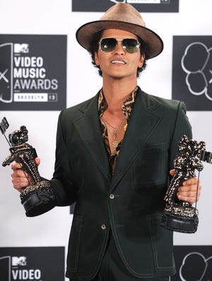 Bruno Mars poses with his best male video and best choreography awards during the 2013 MTV Video Music Awards at the Barclays Center on Aug. 25, 2013.