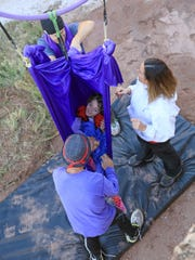 Darren Jeffrey, Summer Davies and Russell Farrell (clockwise from top) surround Zelah Farrell as she swings in a hammock made from aerial fabric in a canyon near Zion National Park.