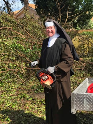 In this Tuesday, Sept. 12, 2017, photo provided by the Miami-Dade Police Department, Sister Margaret Ann holds a chain saw near Miami, Fla. Police said the nun was cutting trees to clear the roadways around Archbishop Coleman Carrol High School in the aftermath of Hurricane Irma.
