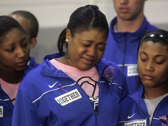 Teammates comfort Keke Stewart before the candlelight