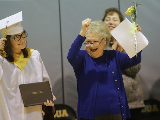 Kelly Muschiatti, 19, moves her tassel to the other side of her graduation cap as Cindy Hayes-Mann, head of Padua Academy, cheers her on.
