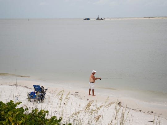 A fisherman tries his luck in Big Carlos Pass just south of Fort Myers Beach.  Dredging equipment sits in the background. The dredging is taking place to ease boat navigation through the popular pass. New Pass will also be dredged. The sand from Big Carlos Pass is being deposited on the beach on the Little Estero Island Critical Wildlife Area. West Coast Inland Navigation is overseeing the dredging.
