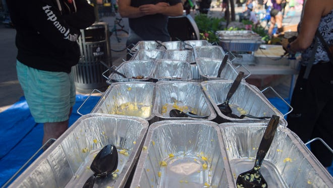 Empty dishes from Illegal Pete's are left behind after cyclists chow down in Old Town Square during Bike to Work Day on Wednesday, June 27, 2018.