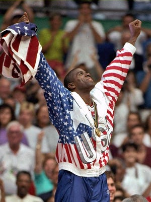 "USA's Earvin ""Magic"" Johnson rejoices with his gold medal after beating Croatia 117-85 in the gold medal game at the Summer Olympics in Barcelona."