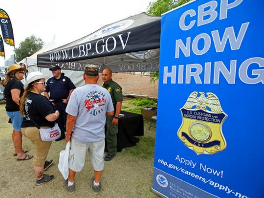 In this April 9, 2017, photo, U.S. Border Patrol agents talk to visitors at a recruitment tent set up at the Country Thunder Music Festival in Florence, Ariz. U.S. Customs and Border Protection, the parent agency of the Border Patrol and of Office of Field Operations, set up the booth at the festival in an effort to hire more agents and customs officers. President Donald Trump has ordered 5,000 new Border Patrol positions.
