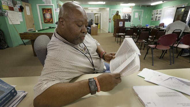 Johnny Hill follows along during Bible study at the Jesus House. A city zoning panel wants to shut down a rehabilitation center that's been helping ex-offenders transition back into society. Jesus House has been operating quietly at 3402 N. Schofield Ave. for nine years in a building that once housed a nursing home.