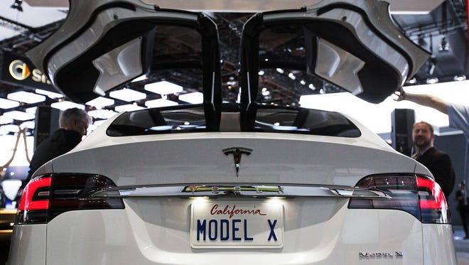 The rear of the Tesla Model X design prototype showing the falcon wing doors on display at the 2013 North American International Auto Show at Cobo Center on Tuesday, Jan. 15, 2013, in Detroit.