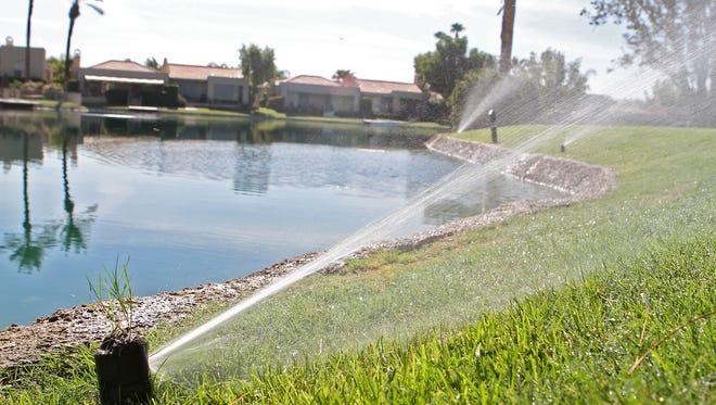 Sprinklers keep a lawn green in a neighborhood in Rancho Mirage.