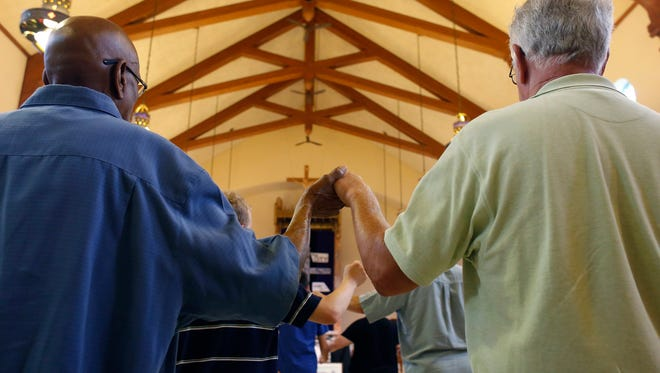 Harry Walker, left, and Mark McGowan, hold hands in prayer during Mass at Christ the King Catholic Church on Sunday, July 23, 2017.
