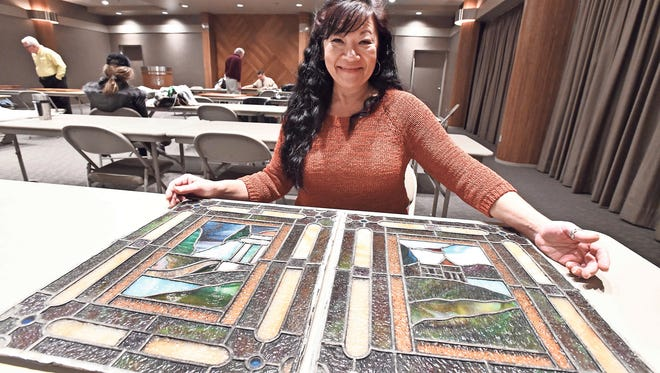 Sandra Hanna with stained glass she found in her home.