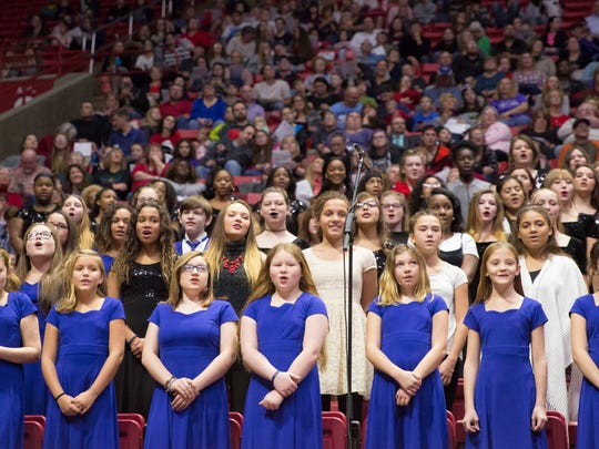 Children with middle school choirs sing two pieces