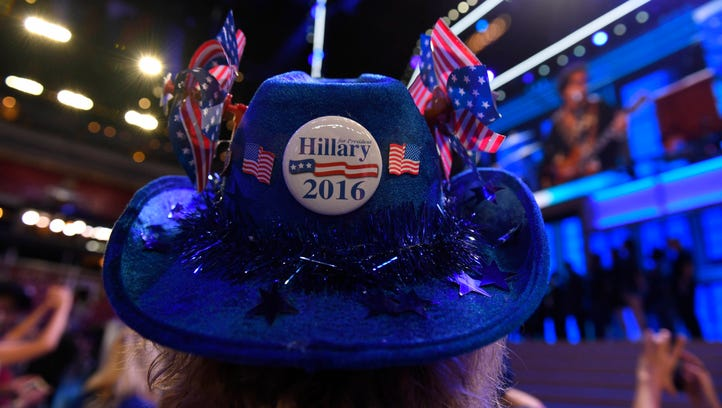A woman wears a hat with a Hillary Clinton pin before