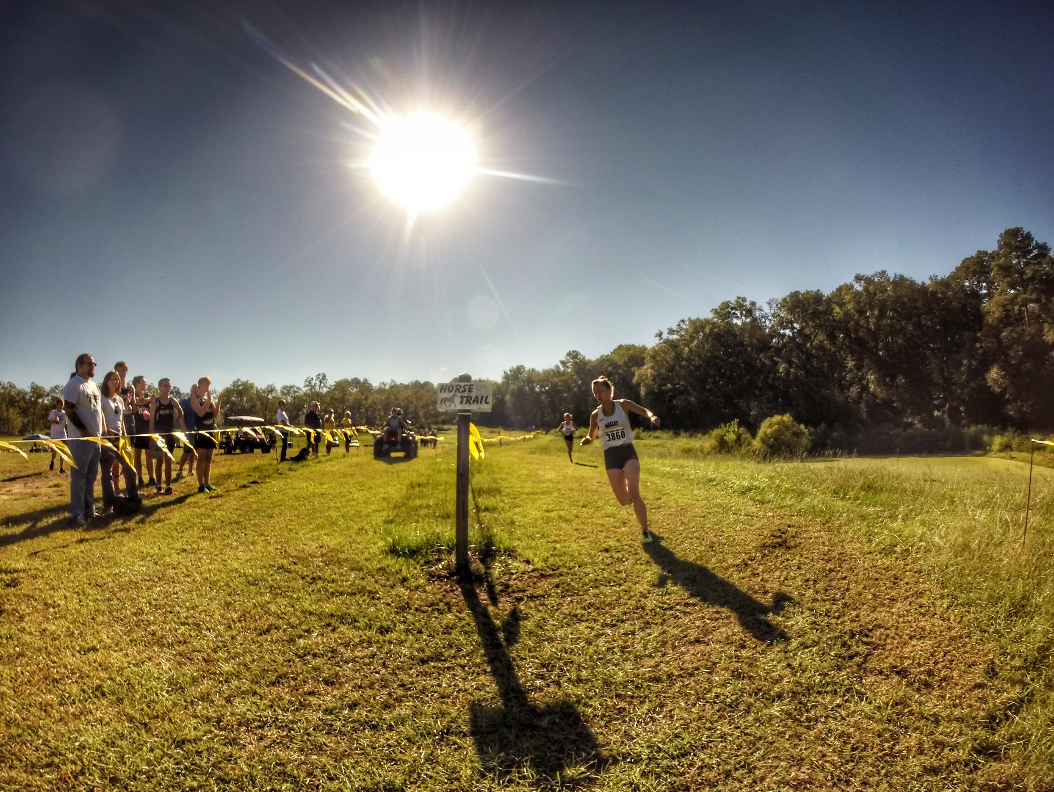 One of the toughest elements of the Aucilla Warrior Stampede is a hairpin curve at the 2.5-mile mark, which Maclay junior Caroline Willis traverses with teammate Lindsay James not far behind.
