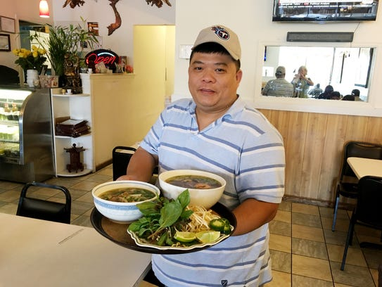 Hung Bui, one of the owners of Kien Giang Vietnamese restaurant on Charlotte Pike, shows off two orders of Pho, along with the condiments that go along with it.