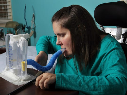 Alisha Waters of Florence, Ky., uses an incentive spirometer