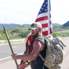 Marine veteran Justin Kuhel walks toward Phoenix Monday (Sept. 15, 2014) on State Route 87 in a trek to raise money and awareness for disabled veterans. He was about 65 miles away.