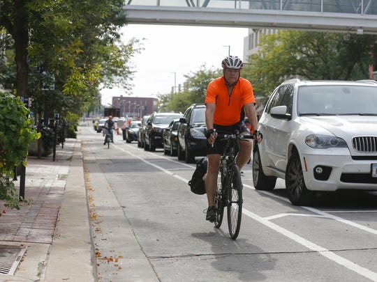 Cedar Rapids police officer Jeff Faircloth uses a protected bike lane downtown on Tuesday, Sept. 22, 2015, in Cedar Rapids, Iowa.