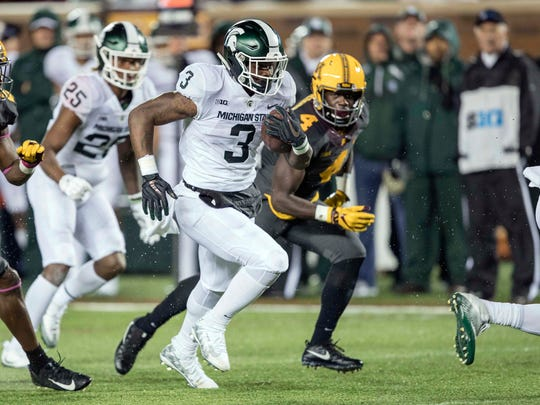 Michigan State running back LJ Scott rushes for one of two touchdowns Saturday at Minnesota.