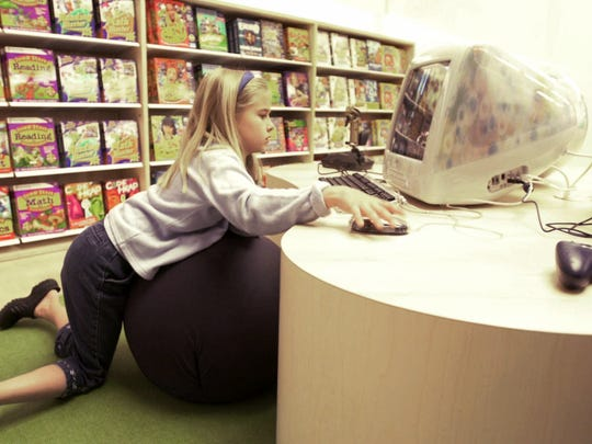 "Morgan McGovern, 8, gets comfortable to work at computers in the ""kids section"" of one of the first Apple retail stores in McLean Va."