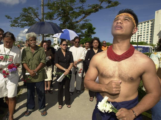 In this April 2003 file photo, Benji Santiago eads an ancestral lineage chant during a memorial service for ancestral remains found at a construction site in Tumon.