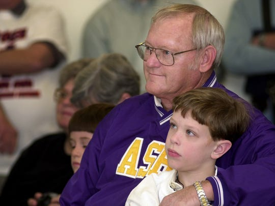 Butch Stoker sits with his grandson Dylon Doyle as he watches his son Scott Stoker (Doyle's uncle) take the position of Northwestern State University's new head football coach.