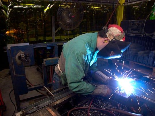 David Rectenwald, 33, of Burlington, welds together