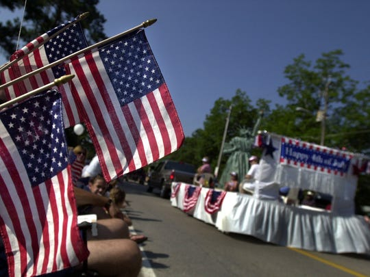 Maedelle Kunkle, of Newberry, S.C., holds flags during the Fourth of July parade at the annual Lexington County Peach Festival Friday, July 4, 2003, in Gilbert, S.C.
