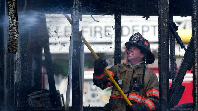 Evansville firefighter Jay Paul pulls down smoldering trim from the front porch of a home at 5513 N. Fares Avenue in Evansville Thursday morning. The home was destroyed and the resident escaped with minor injuries.