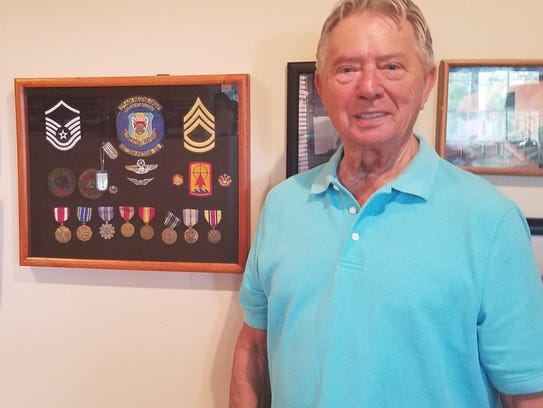 James Pallan stands proudly by a collage of his medals.