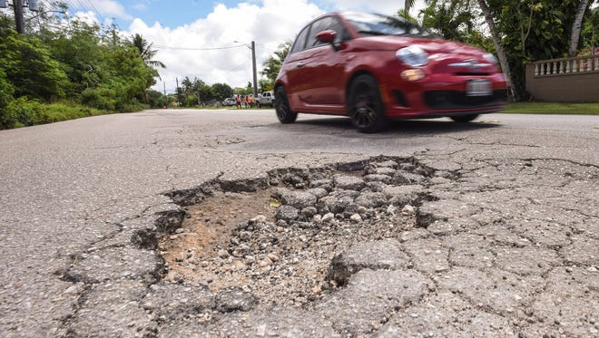 In this May 16 file photo, a motorist tries to avoid one of several potholes on Macheche Road in Dededo