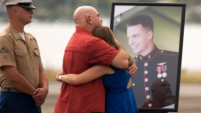 Unidentified family members gather around a photograph of U.S. Marine Lance Cpl. Ty L. Hart, 21, of Aumsville, during a memorial service for the 12 Marines who died when their helicopters crashed off the North Shore of Oahu, Hawaii, Friday Jan. 22, 2016, at Marine Corps Base Hawaii. Servicemen draped flight gear on 12 white crosses Friday to commemorate the Marines who died when two helicopters crashed off the coast of Hawaii during a nighttime training mission. Military members and families gathered for the memorial service at Marine Corps Base Hawaii in Kaneohe after the status of the dozen missing Marines changed to deceased following five days of searching.