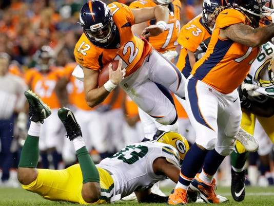 Denver Broncos quarterback Paxton Lynch (12) is upended by Green Bay Packers linebacker Reggie Gilbert (93) during the second half of an NFL preseason football game, Saturday, Aug. 26, 2017, in Denver. (AP Photo/Joe Mahoney)