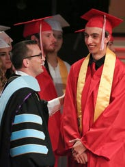 James Bansbach is greeted by Headmaster Timothy Dernlan as he receives his diploma from Red Lion Christian Academy at Reach Church in 2016.