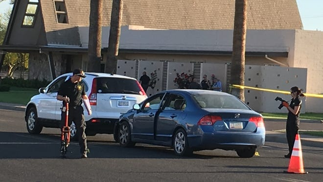 Phoenix police investigate the scene after a pregnant woman driving a blue sedan was fatally shot while with her 6-year-old child.