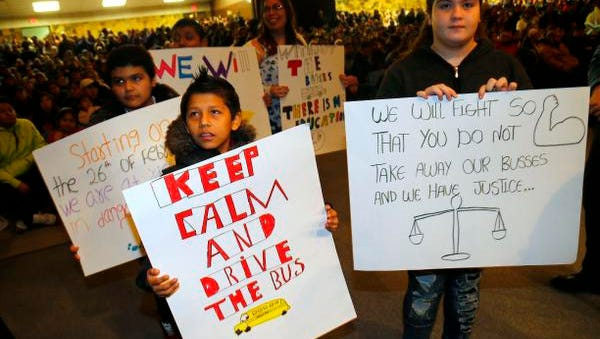 Lakewood students show their signs to board of education members during Lakewood Board of Education meeting at Lakewood High School.Lakewood,NJ. Thursday, February 11, 2016. Noah K. Murray-Special for the Asbury Park Press ASB 0211 busing meeting