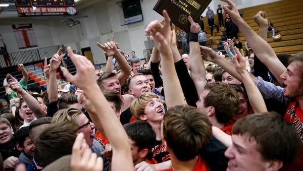 Kaukauna players and fans hold up the sectional champion plaque after the Ghosts beat Appleton North in a boys volleyball sectional final Thursday in Kaukauna.