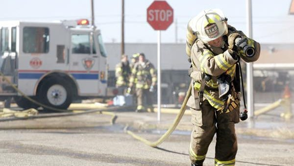 A San Angelo firefighter pulls a fire hose at a scene of a fire.