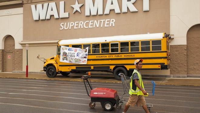 A Walmart employee walks in front of United Way's Stuff the Bus display during the organization's school supply drive in Staunton on Friday, Aug. 1, 2014.