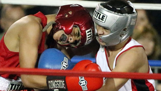 Daniel Trevino, left, and Dominic Stiverson go at it on their 116-120-Pound Junior Olympic bout during the championships of the 2016 Golden Gloves boxing tournament at the El Paso County Coliseum on Sunday. Stiverson won the bout and a first place trophy.