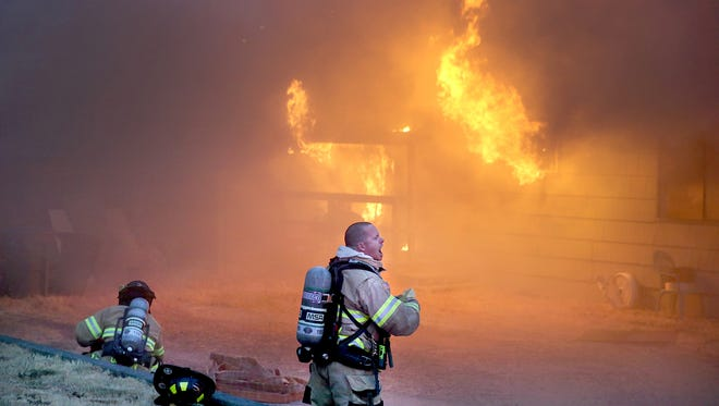 A Bremerton firefighter shouts directions as he and a partner gear up to battle a duplex fire on Hemlock Street in East Bremerton Friday evening.