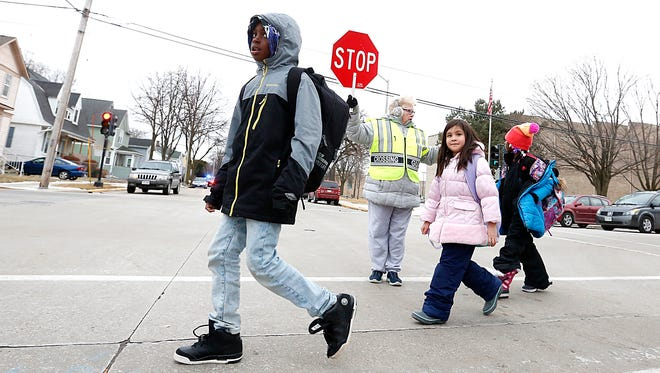 Mary Jean Nicholson helps students of Riverside Elementary School cross the road at Ninth and Linden streets on Jan. 24, 2018. She is one of 17 crossing guards in Fond du Lac.