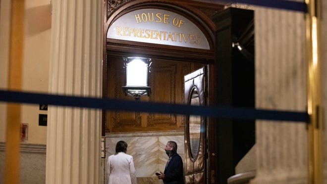As the third day of House debate on policing reform stretched into the night, House Judiciary Chairwoman Claire Cronin and Rep. Paul Tucker, a retired police chief, converse in a chamber entryway.