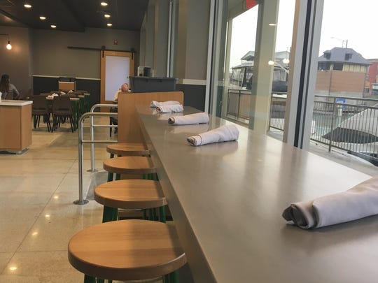 Utensils are set up along a high-top counter overlooking the Black River at the newly-opened TheKitchen cafe on Thursday, Sept. 20, 2018. The restaurant opened in the CityFlats Hotel, which is still slated to be open in spring 2019.