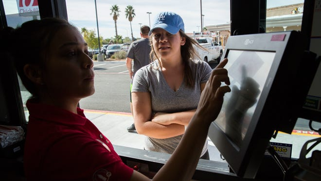 Jenny Logan waits for her order as Chick-fil-A employee in training Amber Perea works the register at the new Lohman Chick-fil-A location on Wednesday, Nov. 16, 2016. Logan was one of 26 people to start camping out in the Chick-fil-A parking lot to take part in the Chick-fil-A First 100, where the first 100 customers gets free food for a year.