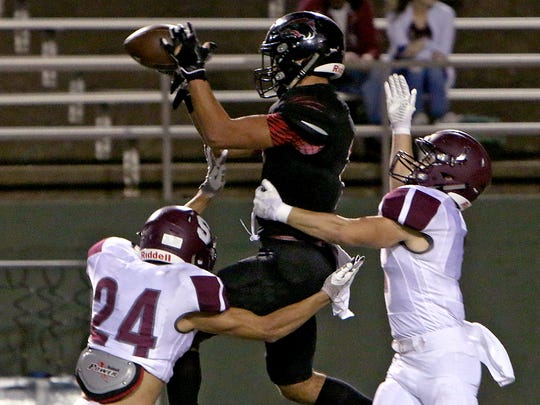 Wichita Falls High's Jordan Hatton (center) makes a leaping catch over Sherman's Austin Bindel (24) and Ben Cross on Friday, Nov. 3, at Memorial Stadium.
